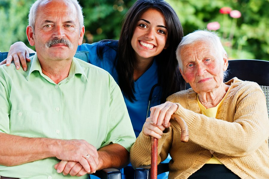 Happy group of people - doctor carer nurse with two patients in the garden of the nursing home.