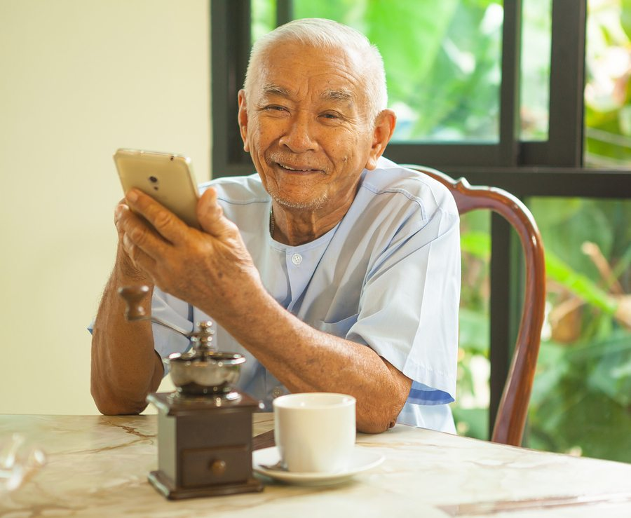 Happy asian senior man using the mobile phone in home