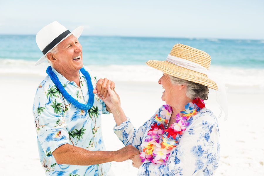 Senior couple dancing together at the beach on a sunny day