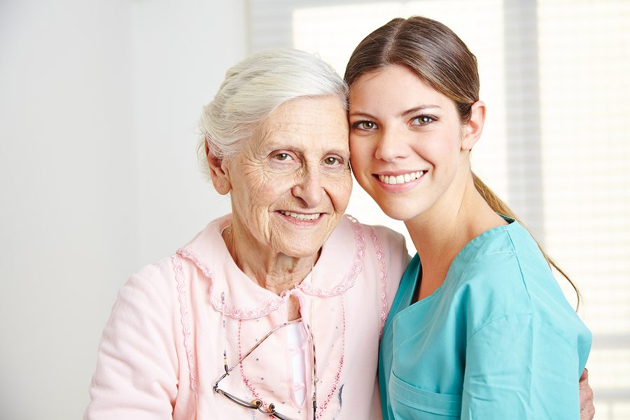 Smiling caregiver embracing happy senior woman in nursing home